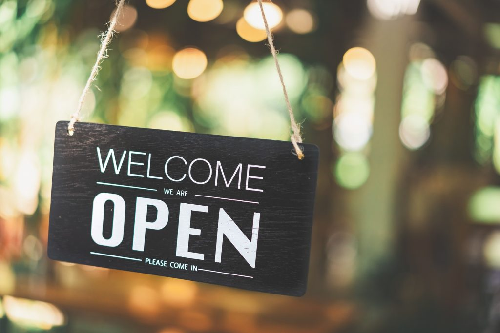 Open sign hanging front of cafe with colorful bokeh light abstract background. Business service and food concept. Vintage tone filter effect color style.