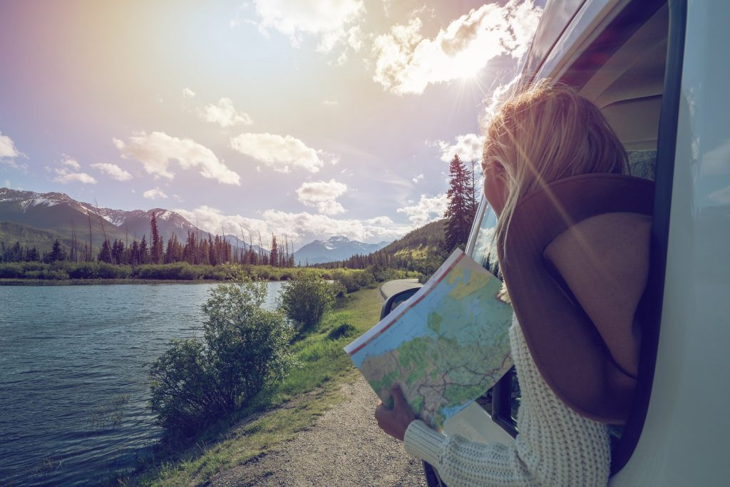 Young woman in car on mountain road looks at map for directions. Mountain lake landscape in Springtime with snow melting.
