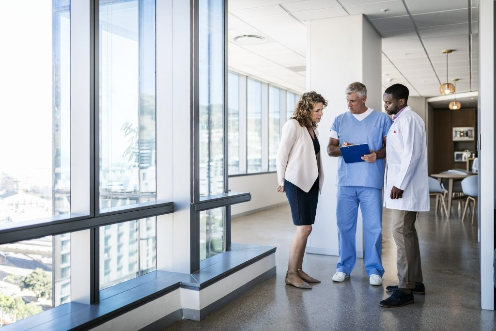 Full length of doctors discussing over clipboard in hospital. Multi-ethnic male and female medical professionals are standing in clinic. Healthcare colleagues are working together.